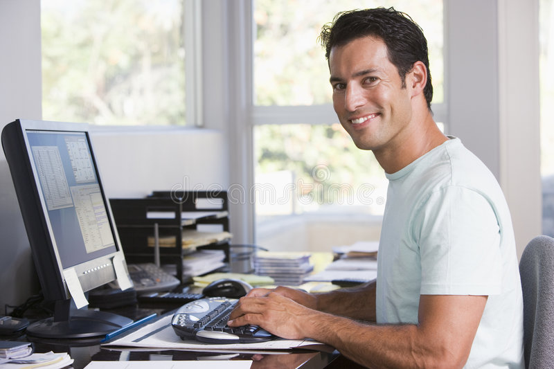 Man in home office using computer and smiling stock photography