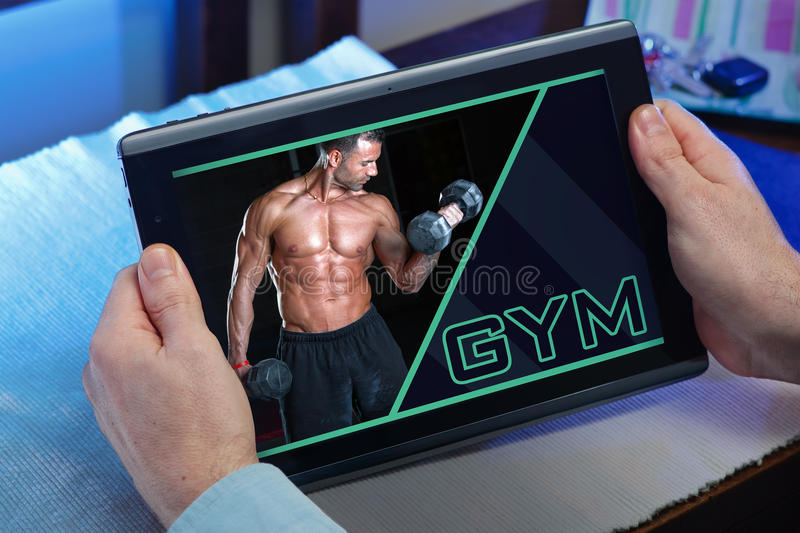 Man at home searching information in internet in gym website for stock image
