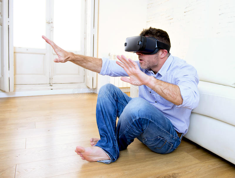 Man at home sofa couch excited using 3d goggles watching 360 virtual reality. Young modern man at home living room sofa couch playing video game excited using 3d stock photo