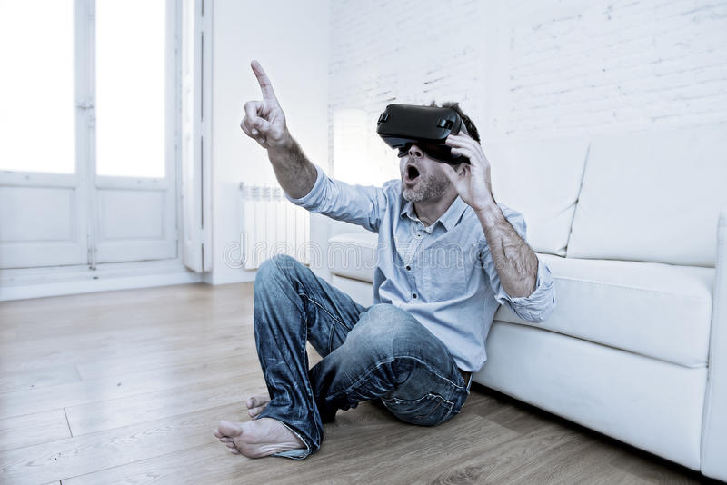 Man at home sofa couch excited using 3d goggles watching 360 virtual reality. Young modern man at home living room sofa couch playing video game excited using 3d royalty free stock images