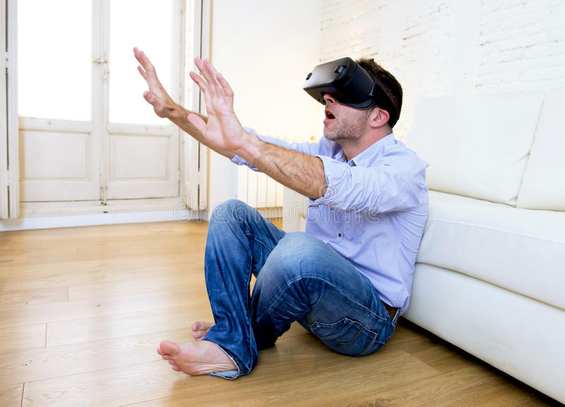 Man at home sofa couch excited using 3d goggles watching 360 virtual reality. Young modern man at home living room sofa couch playing video game excited using 3d royalty free stock photo
