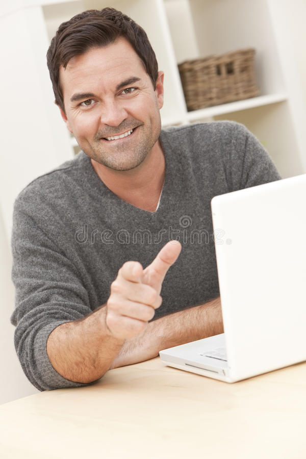 Man At Home Using Laptop Computer And Pointing Royalty Free Stock Image