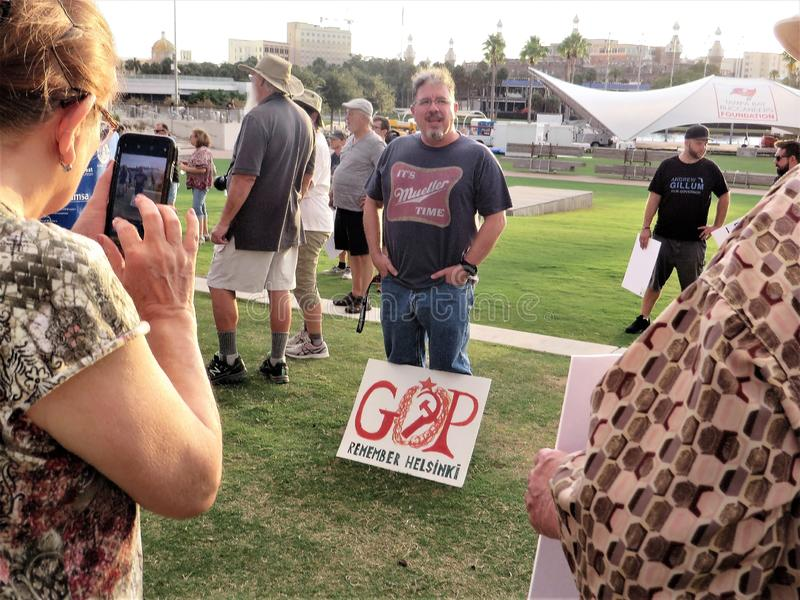 Protestor with signs. Man with homemade red GOP Remember Helsinki sign at MoveOn.org organized demonstration against Trump administration downtown Tampa, Florida stock image