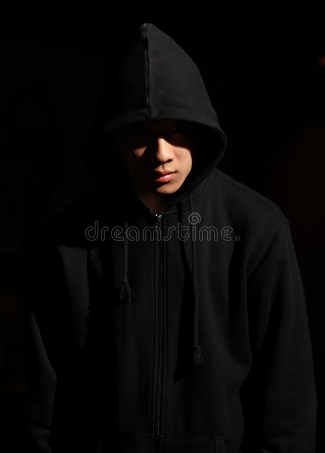 Man in a hood. Monochrome picture of a guy in a hood royalty free stock image