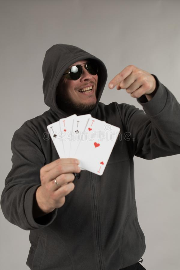 A man in a hood holds playing cards in his hands. And posing on a gray background stock photography