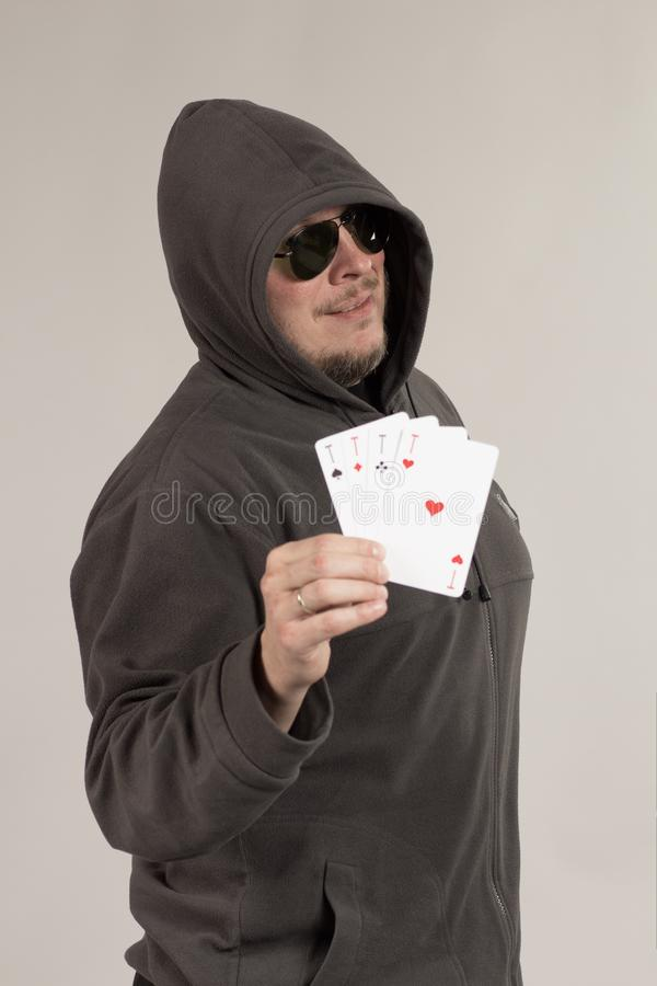 A man in a hood holds playing cards in his hands. And posing on a gray background royalty free stock image