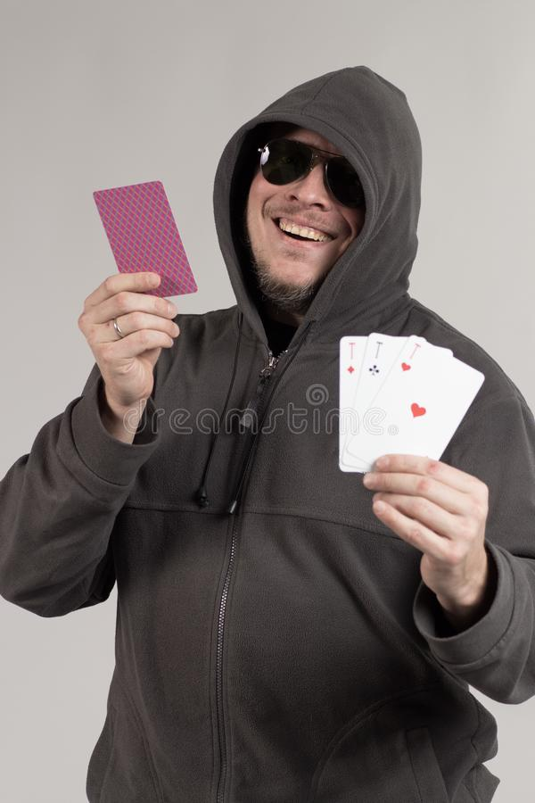 A man in a hood holds playing cards in his hands. And posing on a gray background stock images