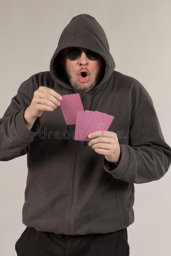 A man in a hood holds playing cards in his hands. And posing on a gray background stock photos