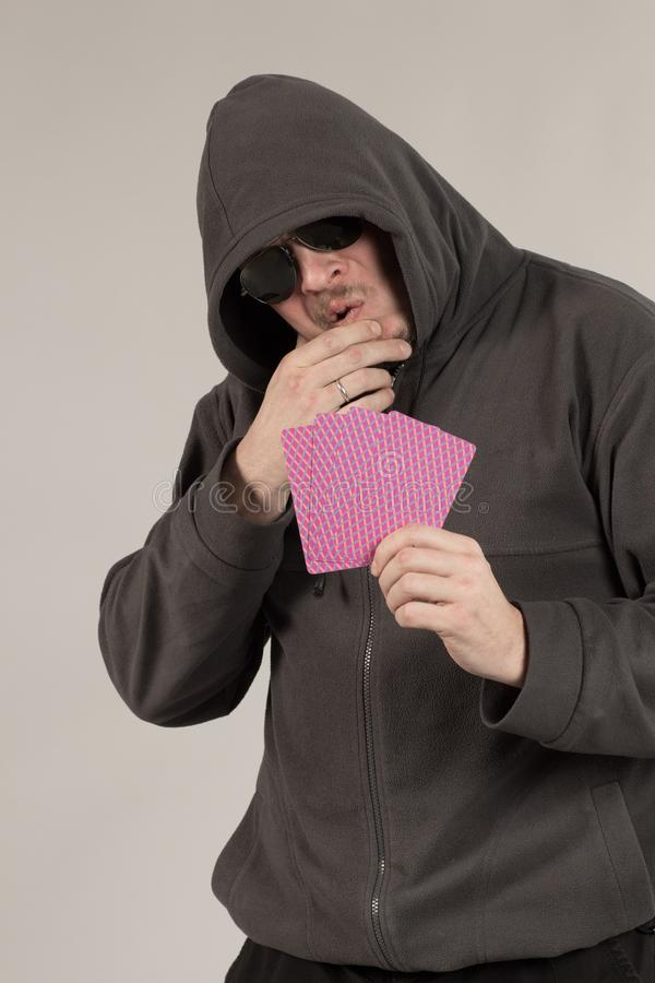 A man in a hood holds playing cards in his hands. And posing on a gray background stock photo
