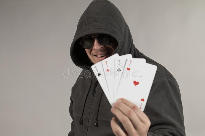 A man in a hood holds playing cards in his hands. And posing on a gray background royalty free stock photography