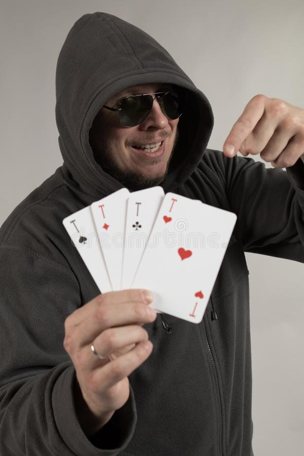 A man in a hood holds playing cards in his hands. And posing on a gray background royalty free stock photo