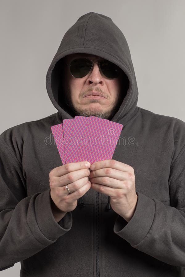 A man in a hood holds playing cards in his hands. And posing on a gray background royalty free stock photos
