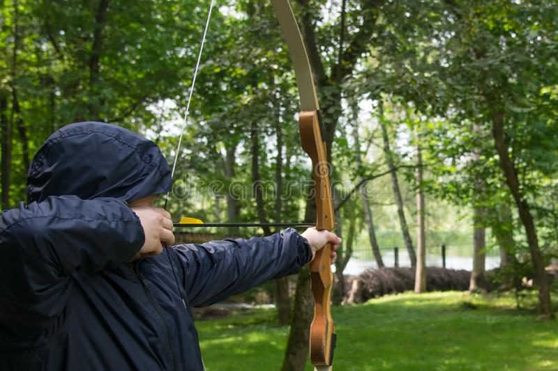 Man in a hood, pulls a bow string and takes aim at a shot at the target. A man in a hood, pulls a bow string and takes aim at a shot at the target stock photo