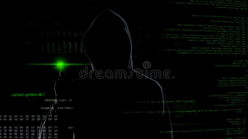 Man in hood push button on virtual screen with scripts, anonymous cyber attack. Stock photo royalty free stock photography