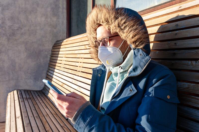 Man with hood sitting alone on bench in sunny weather, wearing facial mask during coronavirus pandemic, using smartphone. Sad man with hood sitting alone on stock images