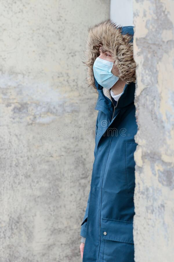Man with a hood wearing protective disposable mask against transmissible infectious diseases. coronavirus/covid-19 pandemic. Unhealthy man with a hood wearing stock photo