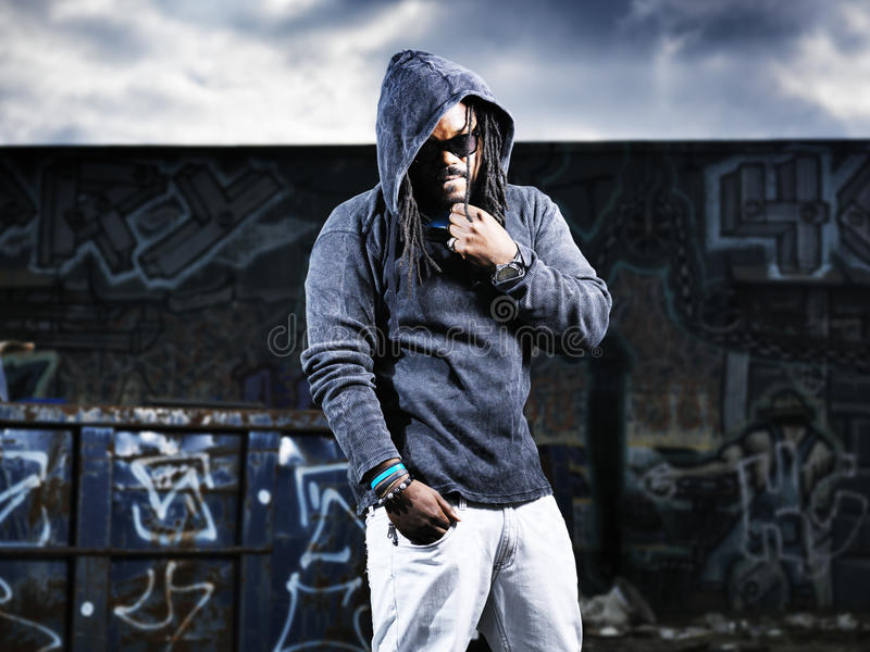 Man in hoodie in front of graffiti stock photography