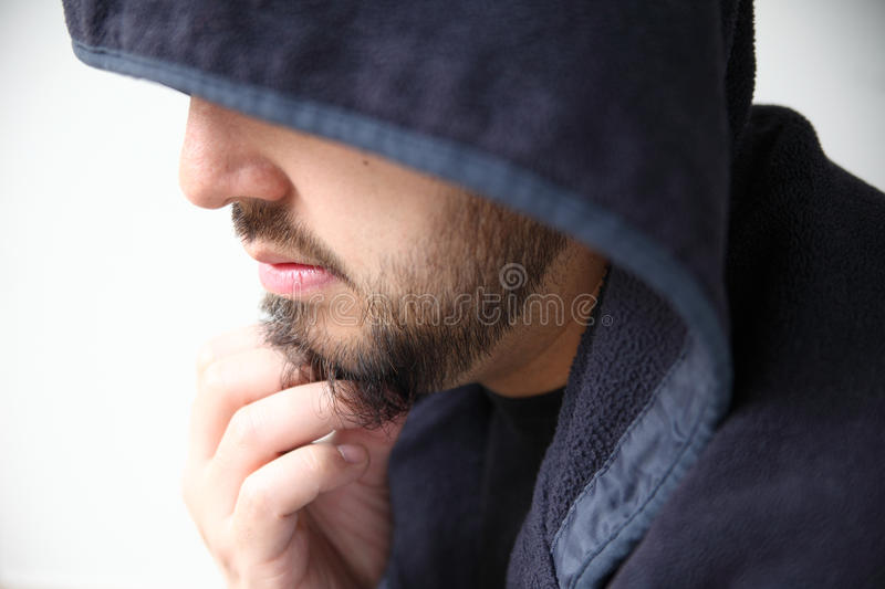 Man in hoodie profile. Young man looks down, hand on beard royalty free stock photo