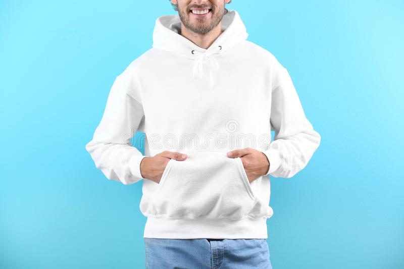 Man in hoodie sweater on color background stock photos