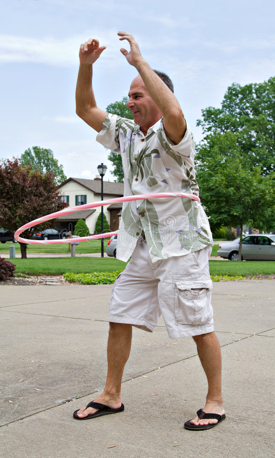 Man Hoola Hoop. A healthy happy mature man plays with a hoola hoop stock photography