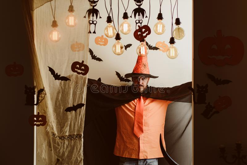 Funny wise wizard on a Halloween background. Handsome man in wizard costume hat for Halloween on fairytale background. Man on the Horror background. Halloween stock photography