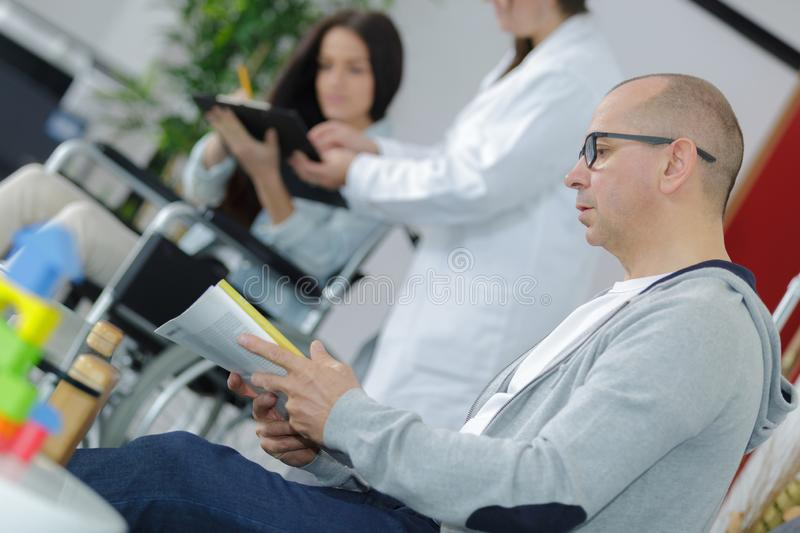 Man in hospital waiting area. Man stock image
