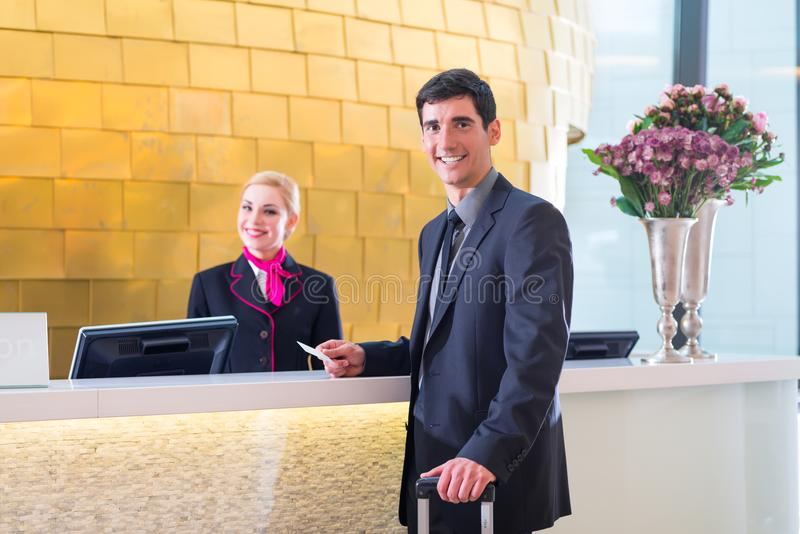 Hotel receptionist check in man giving key card. Man in Hotel check in at reception or front office being given key card stock photo