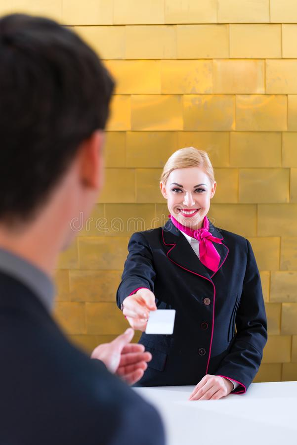 Hotel receptionist check in man giving key card. Man in Hotel check in at reception or front office being given key card royalty free stock photos