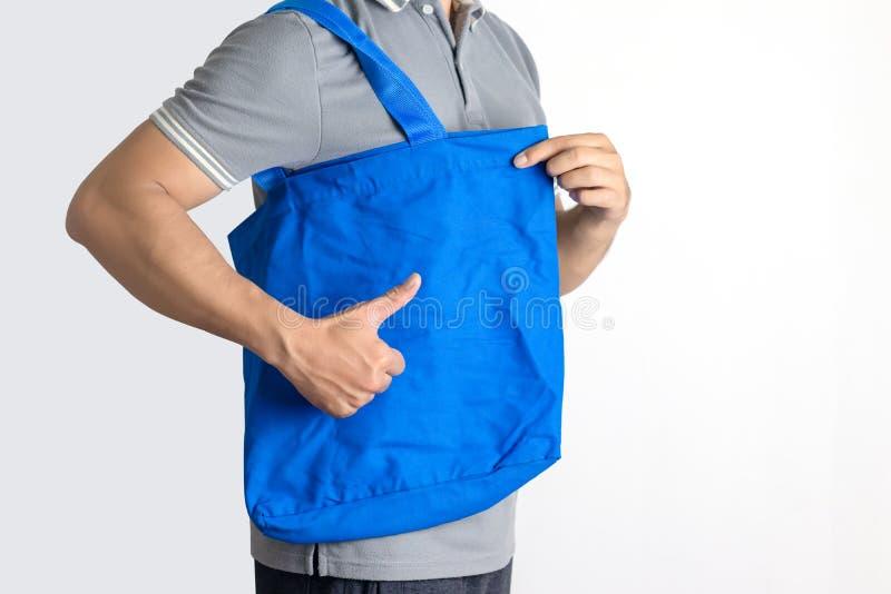 Man houdt blanco doek tote tas Eco-winkeltas stock afbeelding