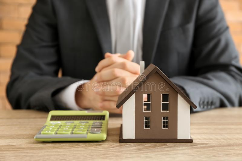 Man with house model and calculator at wooden table. Mortgage concept stock photo