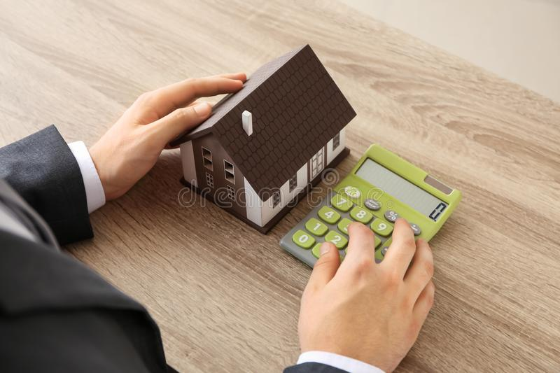 Man with house model and calculator at wooden table. Mortgage concept stock photography