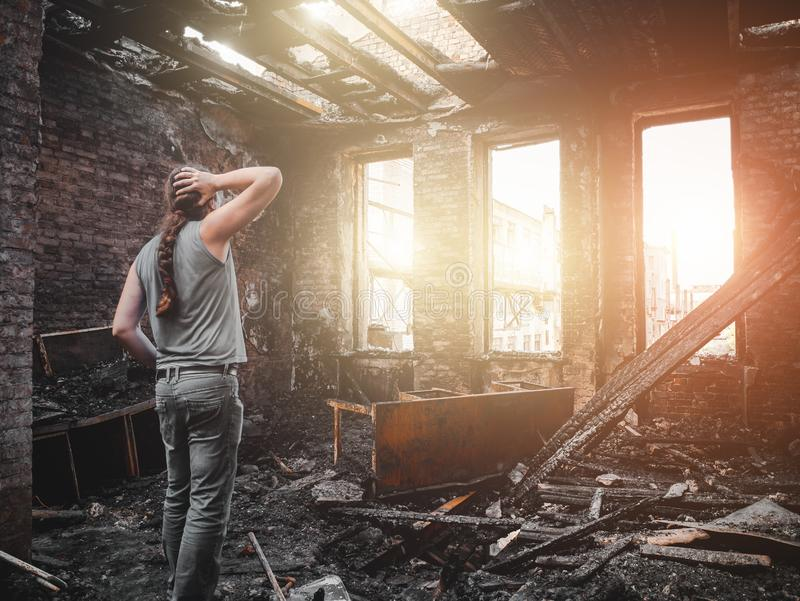 Man house owner stands inside his burnt house interior with burned furniture in arson and holding head by hand, fire aftermath stock image