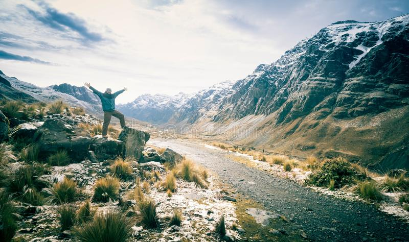 Man on the huge stones looking at valley among rocky Andes range. Man standing on the huge stones and taking pleasure of valley among rocky Andes range stock photography
