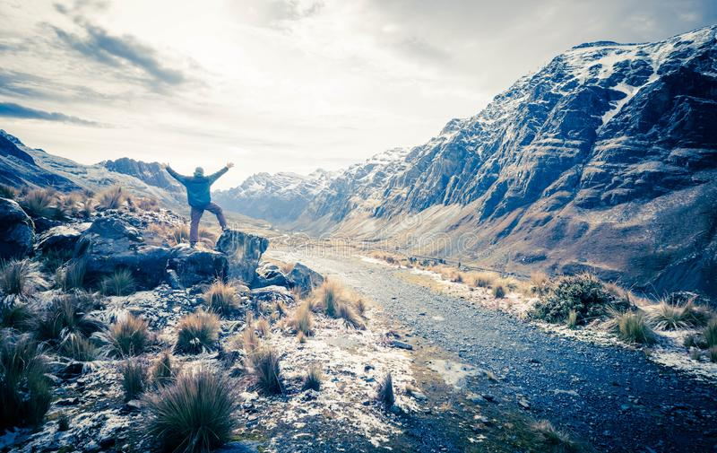 Man on the huge stones looking at valley among rocky Andes range. Man standing on the huge stones and taking pleasure of valley among rocky Andes range stock image