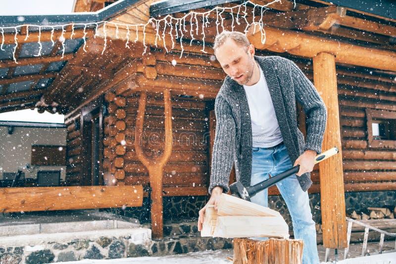 Man hugger trä på snögården för en huskamrat med tungt snöflingor som bakgrund Begreppsbild för vinterlandsidans helgdagar royaltyfri foto