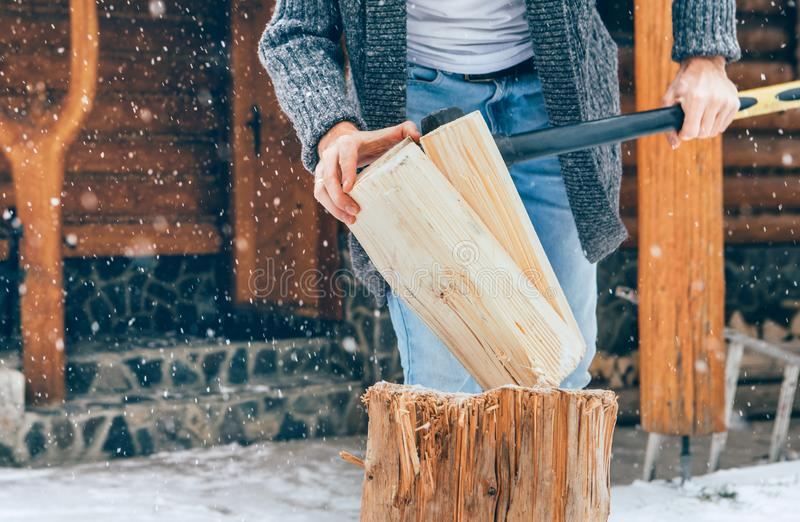 Man hugger trä på snögården för en huskamrat med tungt snöflingor som bakgrund Begreppsbild för vinterlandsidans helgdagar royaltyfri bild