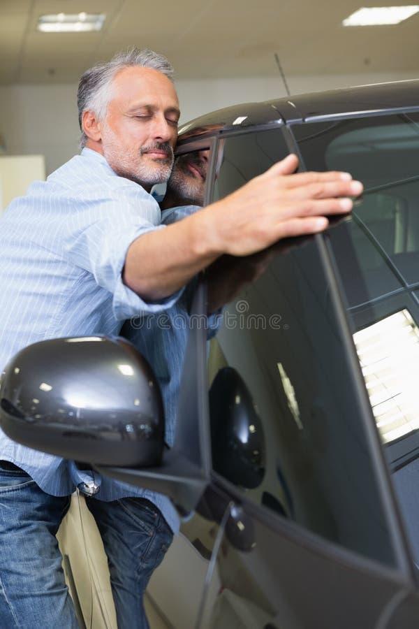 Man hugging on a car. At new car showroom royalty free stock photos