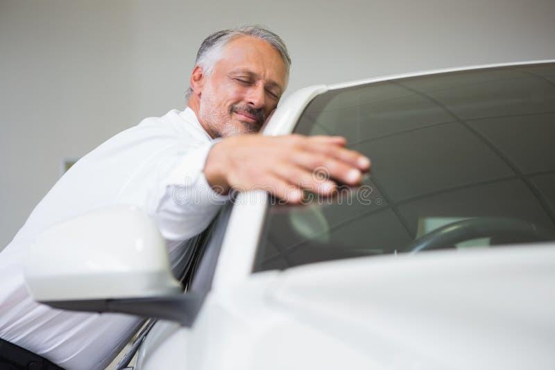Man hugging on a car. At new car showroom stock photos