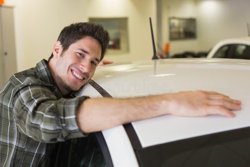 Man hugging on a car. At new car showroom royalty free stock image