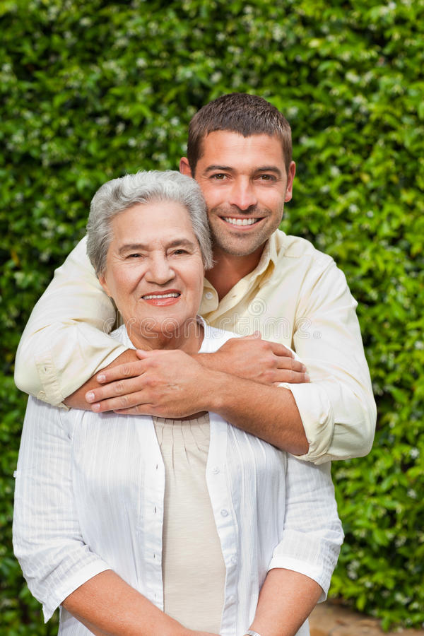 Man hugging his mother in the garden royalty free stock photography