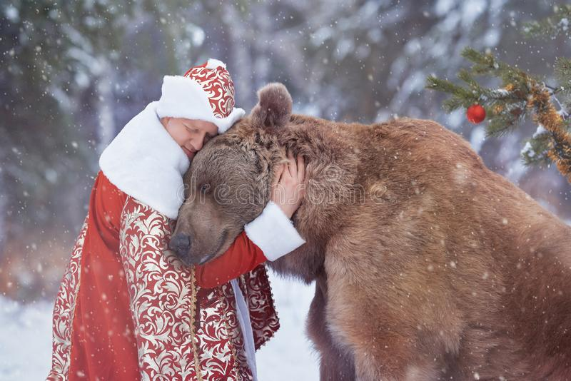 Man hugs brown bear in Christmas eve royalty free stock images