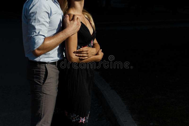 Man hugs girl from behind, on the street, hugging her, attracted to each other. girl in a black dress. man hugs from behind the royalty free stock photography