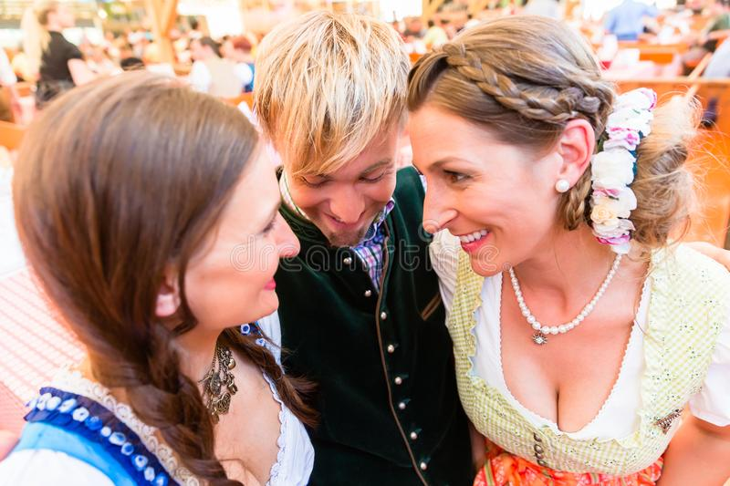 Man hugging two dirndl wearing women in Bavarian beer tent. Man hugs two dirndl wearing women in a beer tent at Bavarian folk fair stock photo