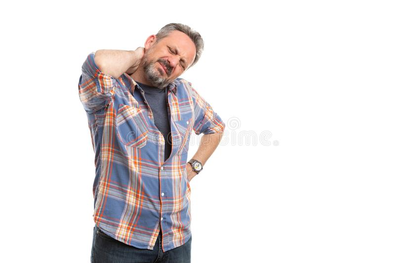 Man touching painful back of neck. Man with hurting expression touching painful back of neck hand  on white studio background stock photos