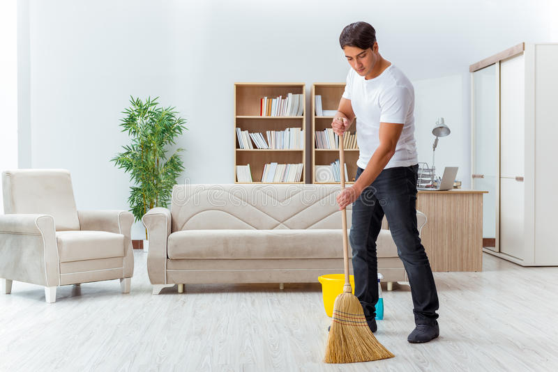 The man husband cleaning the house helping wife. Man husband cleaning the house helping wife royalty free stock image