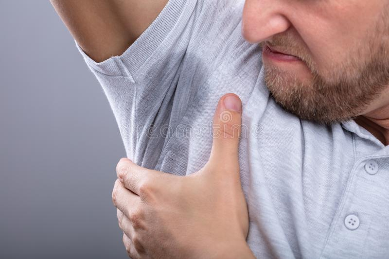 Man Noticing Sweat Under Armpit stock images
