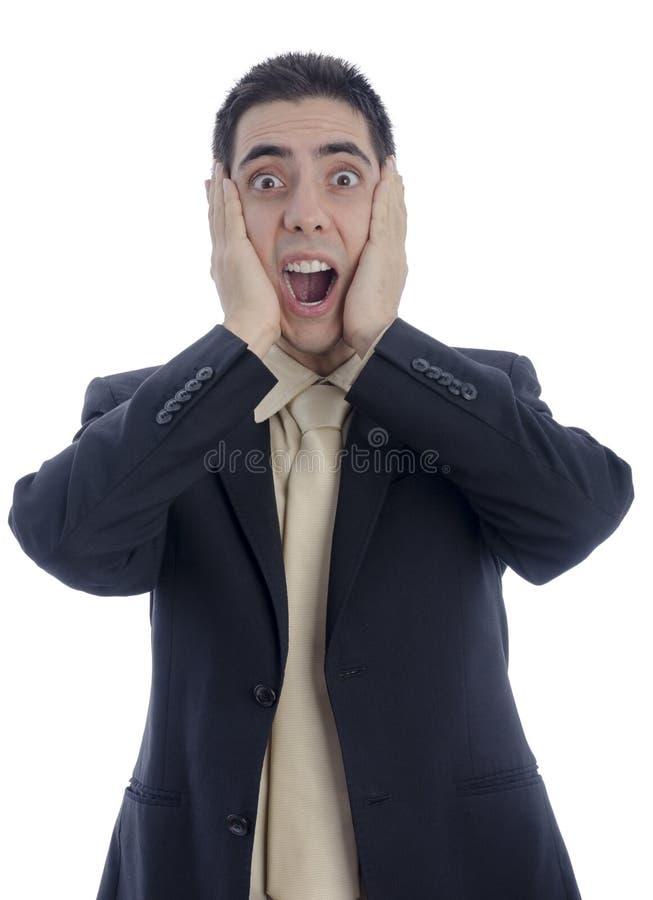 Man i affärsdräkt med hans händer på hans framsida som ropar i desperation fotografering för bildbyråer