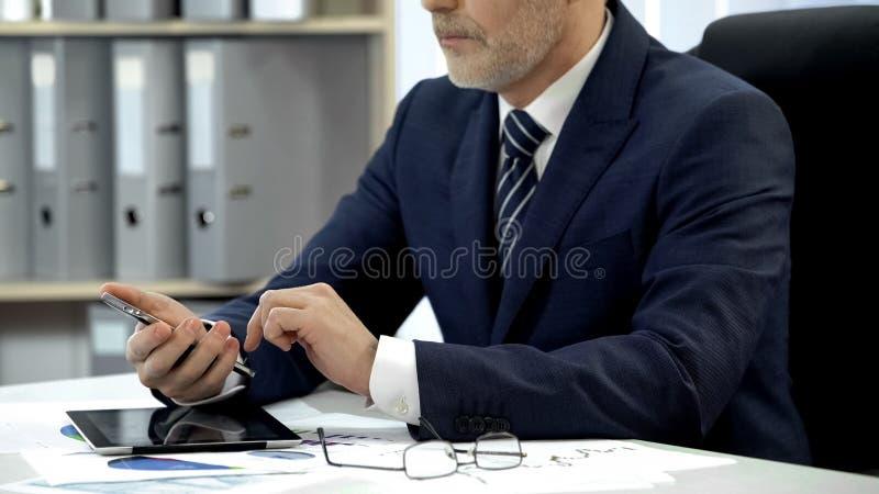 Man i affärsdräkt som i regeringsställning kontrollerar emailen på smartphonen, modern teknologi arkivfoton