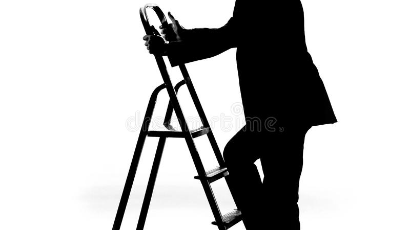 Man i affärsdräkt som upp klättrar karriärstegen som fås jobbbefordran, framsteg arkivfoto
