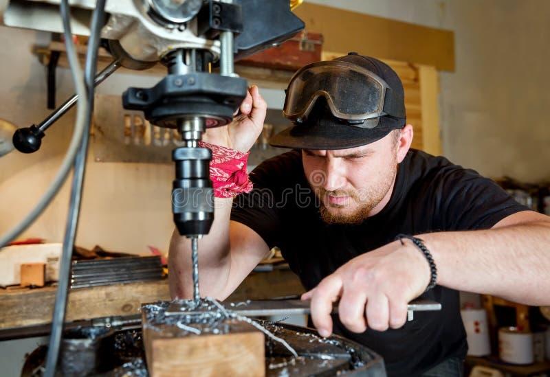 Man i arbete på press för elektrisk drillborr royaltyfria foton